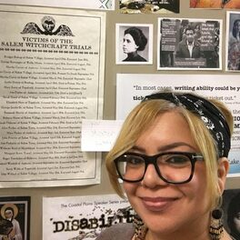 A woman in glasses smiles at the camera; behind her a door bears different pictures of Chicanx and women's history.